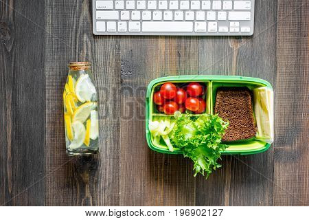 Eat at workplace. Lunch box on dark wooden table background top view