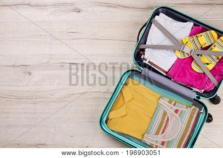 Full opened suitcase, wooden surface. Bag packed with clothing, top view. Concept of summer vacation.