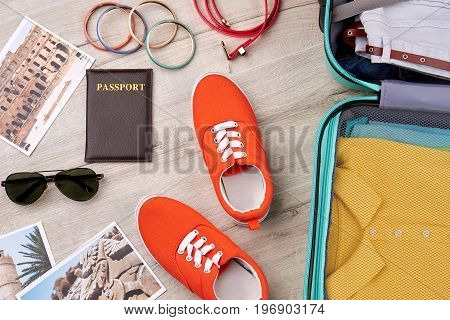 Travelling accessories on wooden floor. Collection of leisure stuff, opened suitcase.