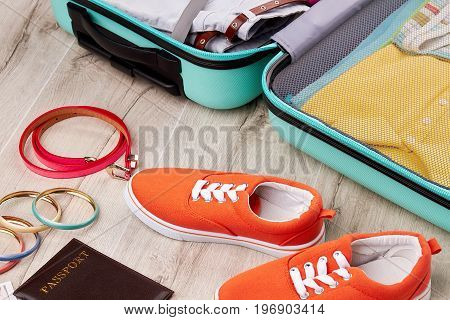 Colored sneakers near opened suitcase. Essential items for summer vacation. Comfortable footwear for trip.