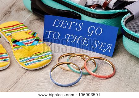 Summer holiday setting, wooden background. Suitcase, slippers, bracelets, paper message.