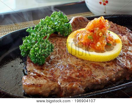 Medium rare steak served on a sizzling platter with a slice of lemon, spices and greens