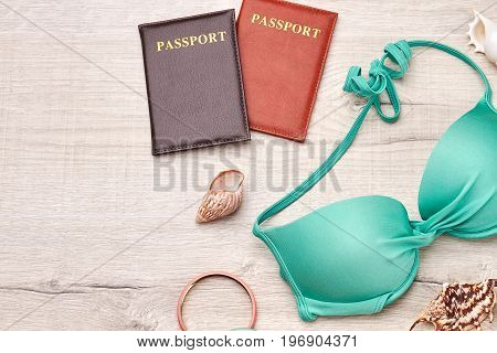 Concept of vacation on tropical seaside. Passports, seashells, accessories, top of swimsuit.