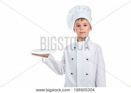 A kid with an empty plate wearing chef uniform on white background. Food and cooking concept.