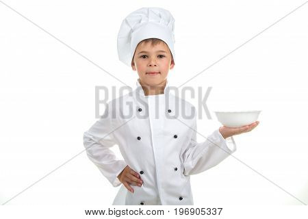 A cute kid with an empty plate on his hand wearing chef uniform, isolated on white background.