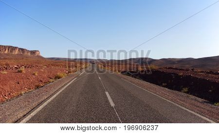 An empty asphalt road in red and stony desert in northern Africa. The sky ist blue and empty the light comes from the right side.