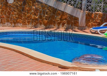 Luxury swimming pool with beautiful landscaping of the territory. In the background a mediterranean wall decorated with sandstones.