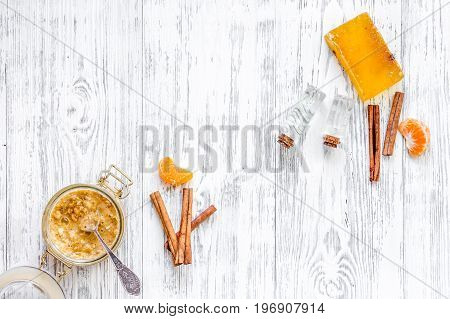 Making organic scrub. Scrub in glass jar, oranges, soap and oil on light wooden background top view.