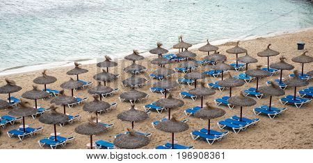 Umbrellas and beach chairs at the beach of Portals Nous