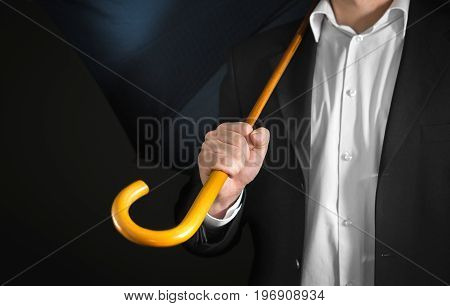 Business man holding umbrella with wooden handle on his shoulder with dark background. Sad unemployment, failure, bankruptcy, over work, burn out and stress concept.