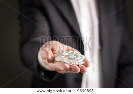 Pharmaceutical representative, consultant or head director or manager of medicine company with white medicine and pills. Man in a suit holding tablets with dark background. Medical business concept.