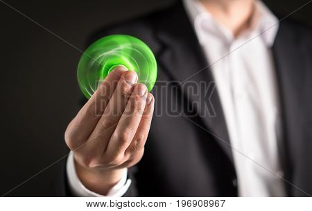 Business man with a fidget spinner. Businessman in a suit holding trendy kids anxiety relief toy in hand.