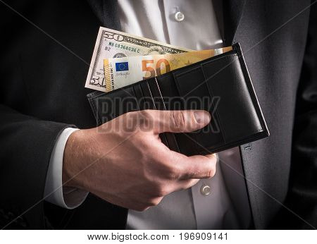 Dollars and euros in wallet. Exchange rate, world economy and financial concept. Business man in a suit with paper money, banknote and bill in hand in both currency.