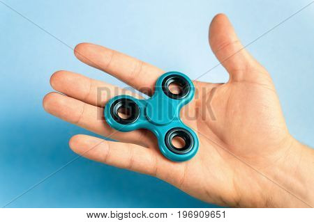 Hand holding fidget spinner with blue background.