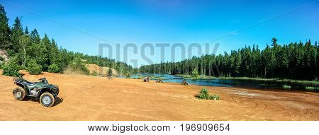 People driving ATV quads on sand beach at lake. Panoramic view. Ontario. Canada.