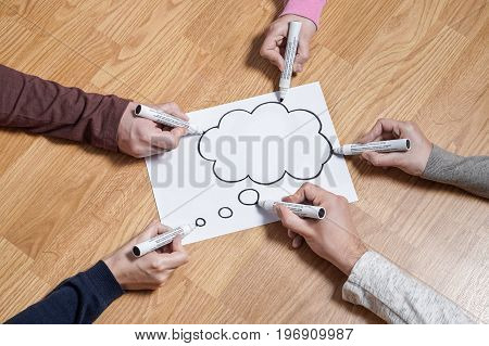 Thinking speech bubble balloon  and thought cloud. Brainstorming new ideas together for marketing plan or school project. Teamwork, synergy and education. Group of people drawing to same paper.