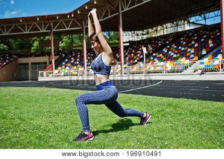 Portrait Of A Beautiful Woman In Sportswear Stretching Her Muscles In The Stadium.