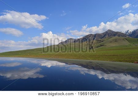 Clouds and Kyrgyzstan mountains reflect on the top of a car. People is paragliding in the distance, enjoying a sunny day.