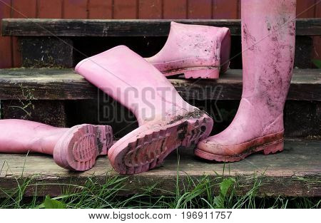 Abandoned dirty pink rubber boots on the wooden stairs. Outdoor cropped photo