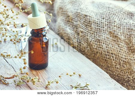 Bundle of dried herbs tarragon bottle of oil and pipette on wooden table near the window burlap rustic style