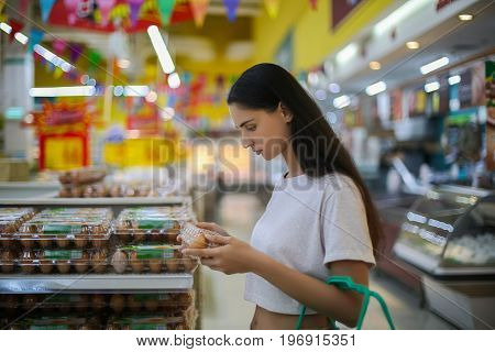 sale shopping consumerism and people concept - woman with food basket at grocery store or supermarket