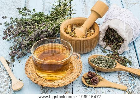 Various dried meadow herbs and herbal tea on light old wooden table. Dried medicinal plants in bag basket mortar and in bundle. Preparing medicinal plants for phytotherapy and health promotion