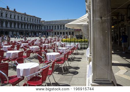 VENICE,ITALY-AUGUST 17,2014:people stroll in the famous saint Mark square in Venice near the bar with the red chairs during a sunny day.