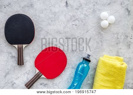 Sport background. Traning cocept. Ping pong racket, towel and water on grey background top view.
