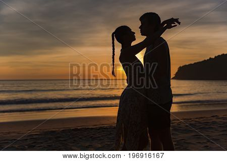 Romantic lovers hugging at twlilight with sunset in background