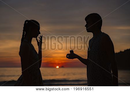 A silhouette man propose marriage to a silhouette woman with sunrise background
