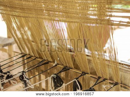 Silk weaving homemade traditional thai fabric. The process of silk weaving in the production of Thai silk in countryside Thailand. selective focus.