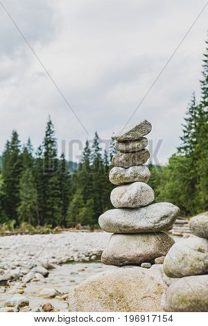 Stones balance hierarchy stack over cloudy sky in mountains. Inspiring stability concept on rocks river and forest.