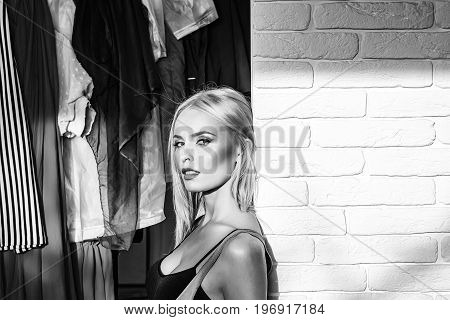 woman in sexy black bustier stands on wardrobe near white brick wall black and white copy space