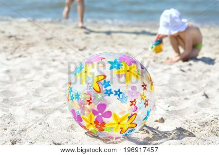 A multi-colored inflatable ball lies on the beach on the sand. The child runs next to the inflatable ball. Summer fun concept.