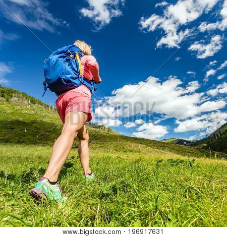 Woman hiking and walking in mountains with backpack. Travel and trekking in beautiful summer nature inspiring health and fitness concept.