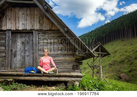Young woman hiker camping drink coffee or tea in beautiful Tatra mountains on hiking trip. Inspirational landscape in Poland. Active girl resting outdoors in summer nature.