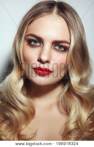 Young beautiful woman with red lipstick and blonde curly hair