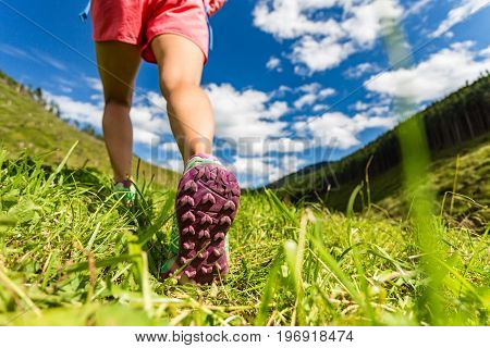 Woman walking in mountains in sport hiking shoes. Jogging trekking or training outside in summer nature. Inspiring health and fitness concept.