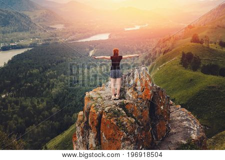 girl traveler stands on the top of the rock of the damn finger in the mountainous Altai, Russia and rejoices. Concept to succeed