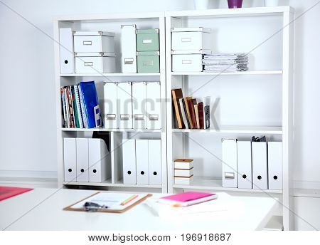 Modern office interior with tables, chairs and bookcases.