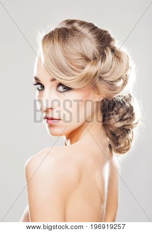 Portrait of gorgeous blond with a beautiful hair style on a grey background.
