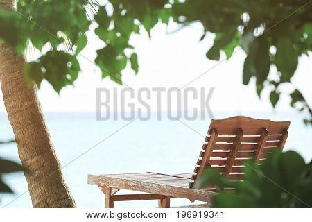 Wooden sun lounger on sea beach in summer day