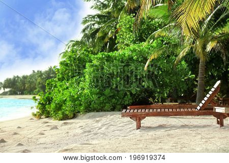 Tropical beach with sun lounger on summer day