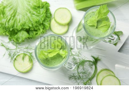 Glasses of fresh juice and ingredients on wooden background