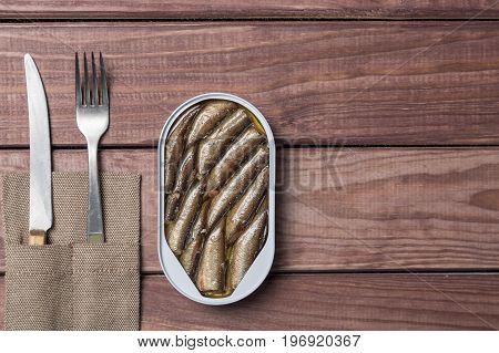 Tin can of spratsfish sardines with knife and fork on wooden table. Top view and free space