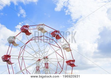 Ferris wheel with the blue sky and cloud in holiday.