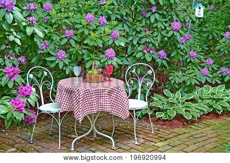 table and chair set in rhododendron garden with fruit basket