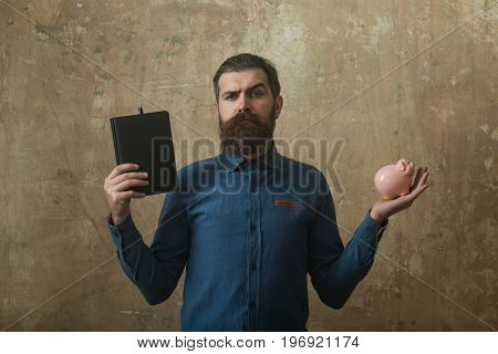 Man With Serious Face Hold Notebook And Money Box