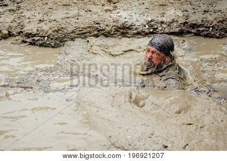A Man Overcomes A Water Obstacle With Dirt During The Power Race Legion Run, Held In Kiev