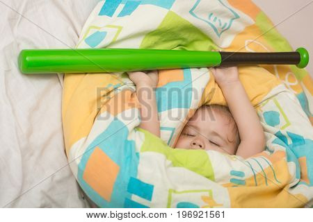 Small baby dreaming. Trust and tenderness. Childhood and happiness. Child sleep in bed with baseball bat. Sleepy baby in colorful blanket.